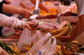 FILE - Customers pay money as they purchase bananas at a market in Beijing, China.
