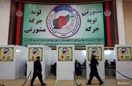 "Members of a traditional Afghan grand assembly convened to debate matters of national importance known as a ""Loya Jirga"" walk inside a registration center in Kabul, Nov. 17, 2013."