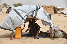 Displaced people fleeing from Boko Haram incursions into Niger are pictured under a makeshift tent in a camp near Diffa on June 16, 2016