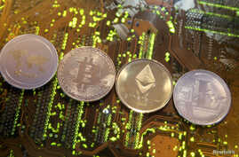 FILE - Representations of the Ripple, Bitcoin, Etherum and Litecoin virtual currencies, Feb. 13, 2018. Switzerland's government wants to look into the feasibility of launching its own state-backed cryptocurrency.