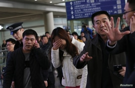 A relative (C, in white) of a passenger onboard Malaysia Airlines flight MH370, covers her face as she cries at the Beijing Capital International Airport in Beijing, March 8, 2014.