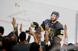 Vegas Golden Knights defenseman Shea Theodore gives his stick to fans after the Knights defeated the Washington Capitals 6-4 in Game 1 of the NHL hockey Stanley Cup Finals Monday, May 28, 2018, in Las Vegas.