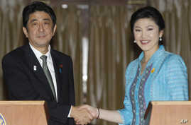 Japanese Prime Minister Shinzo Abe, left, poses with his Thai counterpart Yingluck Shinawatra for photographers at the end of a news conference at the Government House in Bangkok, Thailand, Jan. 17, 2013.