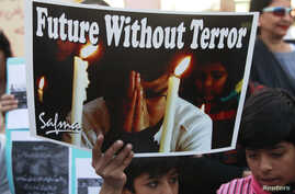 A boy holds a poster during a civil society protest rally against terrorism in Lahore, January 16, 2015.