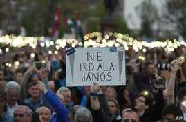 """Demonstrators hold a placard reading """"Don't sign it, Janos"""" referring to President Janos Ader as they protest against the amendment of the higher education law seen by many as an action aiming at the closure of the Central European University, founde"""