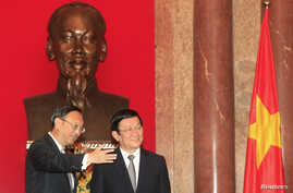 China's State Councillor Yang Jiechi (L) poses for a photo with Vietnam's President Truong Tan Sang in front of a bust of the late Vietnamese revolutionary leader Ho Chi Minh at the Presidential Palace in Hanoi, October 27, 2014. Yang is on a one-day