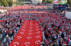 Thousands of demonstrators carry Turkey's national flags during a march against recent Kurdish militant attacks on Turkish security forces, in Ankara, Turkey, Sept. 17, 2015.
