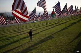 A boy runs among flags flying at Pepperdine University in honor of the victims of the September 11, 2001 attacks, Malibu, California, September 10, 2012.