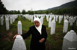 Mejra Dzogaz touches the graves of her two sons before the television broadcast of the court proceedings of former Bosnian Serb general Ratko Mladic's in Potocari, near Srebrenica, May 17, 2012. Mejra's husband, three sons and a grandson were killed