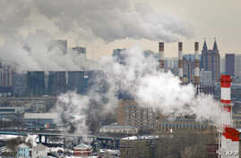 FILE - An aerial view of Moscow, with steam and smoke rising cooling towers and chimneys of  a coal-fired power plant in the foreground.