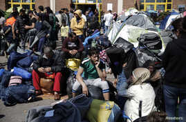 Refugees and migrants sit next to their belongings before boarding a bus heading to other parts of the country where they will be accommodated, at the port of Piraeus, near Athens, Greece, March 31, 2016.