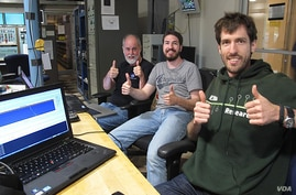 """Reboot team at NASA Ames """"McMoons"""" control room gives a """"thumbs up"""" once gaining control of the decommissioned satellite.  (ISEE-3 Reboot Project)"""