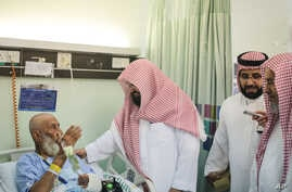 Sheikh Abdul Rahman Al Sudais, the imam of the Grand Mosque in Mecca, talks to one of the injured in the Sept. 11, 2015 crane accident at the mosque, at a hospital in Mecca, Saudi Arabia, Sept. 13, 2015.