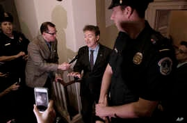 FILE - Sen. Rand Paul, R-Ky. holds an impromptu news conference outside a room on Capitol Hill in Washington where he charged House Republicans were keeping their Obamacare repeal-and-replace legislation under lock and key and not available for publi