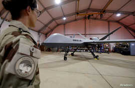 FILE - A French soldier of the regional anti-insurgent Operation Barkhane stands in front of a General Atomics MQ-9 Reaper drone version Block 1 in Niamey, Niger, Oct. 21, 2017.