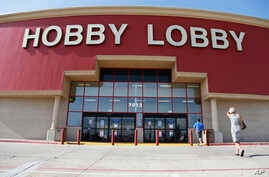 FILE - In this June 30, 2014, file photo, customers walk to a Hobby Lobby store in Oklahoma City. Federal prosecutors say Hobby Lobby Stores has agreed to pay a $3 million federal fine and forfeit thousands of ancient Iraqi artifacts smuggled from th