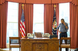 President Barack Obama talks on the phone in the Oval Office with Russian President Vladimir Putin about the situation in Ukraine, March 1, 2014.