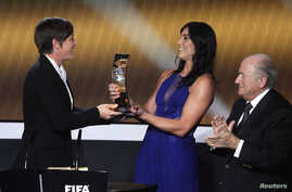 FILE - Sepp Blatter, then the head of FIFA, applauds as Hope Solo, second from right, presents a trophy to fellow soccer player Abby Wambach during the FIFA Ballon d'Or 2012 awards ceremony in Zurich, Jan. 7, 2013. Solo now says Blatter groped her ju
