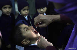 A female polio worker gives polio vaccine drops to a child in Lahore December 20, 2012. An alliance of Pakistani clerics will hold demonstrations across the country against the killings of polio eradication campaign workers, leaders said on Thursday,