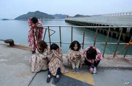 Relatives wait for their missing loved ones at a port in Jindo, South Korea, Wednesday, April 16, 2014.