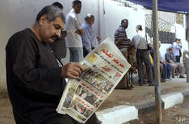 """A man reads a local newspaper with the headline in Arabic reading, """"Egypt surprises the world,"""" outside a polling station in Cairo, May 27, 2014."""