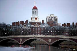 FILE - Rowers paddle down the Charles River past the campus of Harvard University in Cambridge, Mass., March 7, 2017. A federal judge in Boston heard closing arguments Friday in a highly publicized lawsuit alleging that elite Harvard discriminates ag...