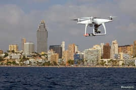 A drone, equipped with a camera used by police for surveillance tasks, flies in front of Poniente beach at the eastern costal town of Benidorm, Spain, Aug.18, 2016.