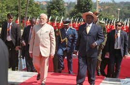 Indian Prime Minister Narendra Modi, centre left, is received by President Yoweri Museveni, centre right, after inspecting a parade at State House Entebbe,  about 42 Km from the capital Kampala Monday July 24, 2018.  Modi has embarked on a five-day t