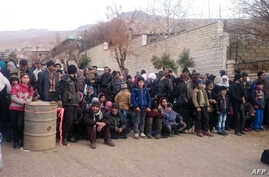 Syrians wait for the arrival of an aid convoy, Jan. 11, 2016, in the besieged town of Madaya as part of a landmark six-month deal reached in September for an end to hostilities in those areas in exchange for humanitarian assistance.