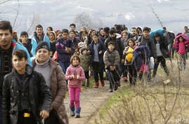 Refugees and migrants, mostly from Afghanistan, walk towards the transit center for refugees near the northern Macedonian village of Tabanovce, after being returned from Serbia, Monday, Feb. 22, 2016.