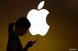 A woman looks at the screen of her mobile phone in front of an Apple logo outside its store in downtown Shanghai, China, Sep. 10, 2013.