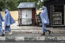 FILE - Girls walk home after school in Maiduguri on July 5, 2017.