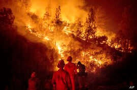 FILE - Firefighters monitor a backfire while battling the Ranch Fire, part of the Mendocino Complex Fire near Ladoga, Calif., Aug. 7, 2018. A nationwide telecommunications company that slowed internet service to firefighters as they battled the large