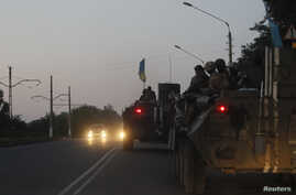 A convoy of Ukrainian armored personnel carriers drive on a road in Kramatorsk, Ukraine, Aug. 19, 2014.