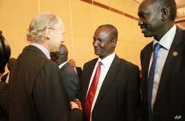 Mahaboub Maali, chief negotiator from South Sudan's opposition, center, shakes hands with an unidentified western observer in Addis Ababa, Ethiopia, Jan. 4, 2014.