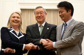 U.S. Secretary of State Hillary Rodham Clinton, left, South Korean Foreign Minister Kim Sung-hwan, center, and Japanese Foreign Minister Koichiro Gemba shake hands before their trilateral meeting during the ASEAN Regional forum in Phnom Penh, Cambodi