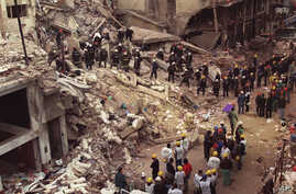 FILE - In this July 18, 1994 file photo, firefighters and rescue workers search through the rubble of the Argentine-Israeli Mutual Association community center, after a car bomb rocked the building in downtown Buenos Aires, Argentina.