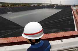 A worker stands in front of a newly installed fresh water reservoir, used to cool down nuclear reactors in case of emergencies, at Tokyo Electric Power Co.'s (TEPCO) Kashiwazaki Kariwa nuclear power plant, which is the world's biggest, in Kashiwazaki