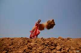 FILE - Indian woman Shanti Patel helps dig a water reservoir at the edge of an open coal mine in Sarasmal village near the industrial city of Raigarh, in Chhattisgarh state, India, April 15, 2014. While India's rapid economic growth over the past dec