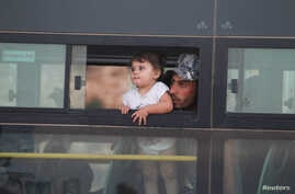 A Syrian man with a child is seen in a bus in Jroud Arsal, Lebanon Aug. 2, 2017.