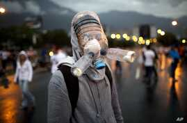 Protester in gas mask made from plastic water bottles helps block highway to airport, Caracas, Venezuela, Feb. 18, 2014.