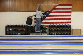 Workers take down a U.S. flag following a campaign stop by Democratic presidential candidate Hillary Clinton at the Family Fun Center in Adel, Iowa, Jan. 27, 2016.