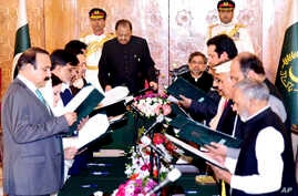 In this photo released by Pakistan's Press Information Department, Pakistan's President Mamnoon Hussain, front on left, administers oath to ministers in Islamabad, Pakistan, Aug. 4, 2017.