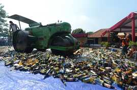 A steam roller machine destroys hundreds of alcohol drinks, pornographic and pirated video DVDs in a Jakarta police station, July 8, 2013.