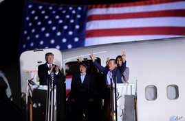 President Donald Trump, from left, greets Tony Kim, Kim Hak Song, seen in the shadow, and Kim Dong Chul, three Americans detained in North Korea for more than a year, as they arrive at Andrews Air Force Base in Md., May 10, 2018. First lady Melania T