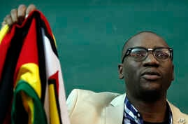 FILE - Zimbabwean Pastor Evan Mawarire holds his country's flag before addressing supporters at the University of the Witwatersrand in Johannesburg, South Africa, July 28, 2016.