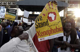 "FILE - A man holds a poster reading ""we stand against xenophobia""  during a march in Johannesburg, South Africa, protesting against recent attacks on immigrants that killed seven people, April 23, 2015."