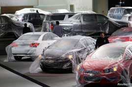 FILE - Newly-produced American vehicles are seen covered with protective wrap at an expo center in Detroit, Michigan.