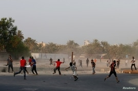 Protesters throw stones during clashes with riot police in village of Shakhoora, west of Manama, Aug. 14, 2013.