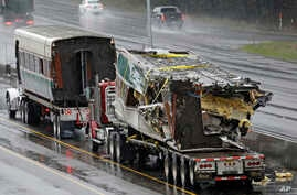 Two damaged train cars sit on flatbed trailers after being taken from the scene of an Amtrak train crash in DuPont, Washington, Dec. 19, 2017.
